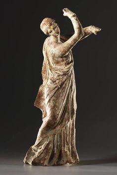 A Statuette of a Dancer.H. 23.3 cm. Clay, white, pink, blue paint. Greek, Hellenistic, ca. 250 B.C.