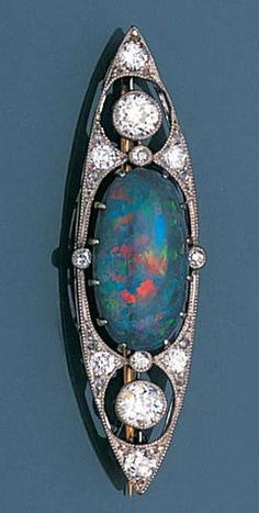 A black opal and diamond brooch, circa 1905 Spindle-shaped, claw-set to the centre with an oval cabochon black opal, within an openwork surround, millegrain-set with old brilliant, single and rose-cut diamonds, later pin fitting, length 4.8cm.