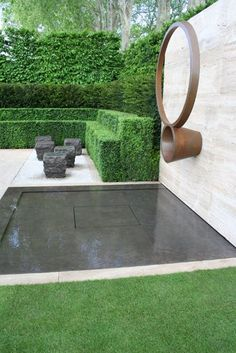 Perfectly proportioned water features punctuate the design: in addition to the reflecting pool beneath the sculpture, simple pools cut into the blocks of hornbeam lead the eye out of the garden and emphasize the tranquillity of the setting.
