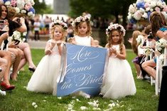 """Precious flower girls with """"Here comes the bride"""" sign"""