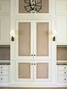 Suede paneled doors with French brass tacks.