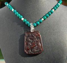 Jade Dragon pendant with Azurite-Malachite, Pearl and Sterling Silver Necklace.Beautifully carved bas relief Chinese Dragon on gorgeous deep red brown jade swings from a necklace of brilliant green and sky blue azirite-malachite and soft creamy white freshwater pearls. The dragon holds the the Pearl of Wisdom.The pendant is 2 inches by 1 1/2 inches with a 2 1/2 inch drop. The necklace is approximately 18 inches long with a 3 3/4 inch sterling silver extender chain and a sterling silver ...