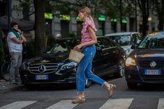 Veronika Heilbrunner wears a Miu Miu ruffle blouse, raw hem jeans, Gucci clogs, and a straw bag