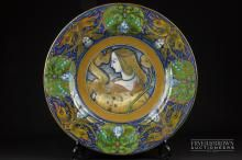 A Cantagalli maiolica charger in Deruta style, decorated with central design of a young lady with ribbon banner, inscribed VIRE SLSE, within a border of fabulous beasts and putto heads, blue painted cockerel mark, numbered 26, stamped Firenze, 40cm diameter