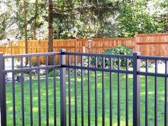 Black ornamental aluminum 3 rail fence with custom built high cedar privacy fence in background. Aluminum Fence, Rail Fence, Michigan, Deck, Yard, Exterior, Ornaments, Building, Outdoor Decor