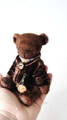 Mr.George - 14,5 cm bear made of brown vintage plush, has got 5 joints (double for the head), glass eyes, loosely embroidered nose, stuffed with fibrefill and steel pellets , shaded with oil paint. He wears a jacket with watch pendant, on the neck he has a satin scarf.