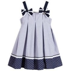 Girls lovely dress by Lapin House, featuring large navy blue and white grosgrain bows on the shoulders, one with the designer's silver metal, logo heart charm. Made in a soft, cotton blend, the dress has a textured blue stripe and inverted pleats all around, with an anchor-printed, navy blue border by the hemline. There is a concealed zip fastener at the back.