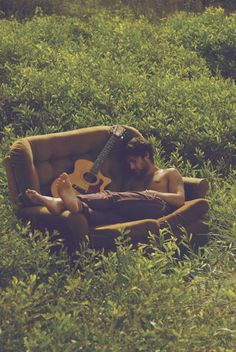 sleeping bearded man with guitar on sofa in nature. If I moved my couch to the park this is my luminous life.