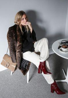 Mulher posa para foto sentada em mesa de café usando tricot preto, casaco de pelos com estampa de onça, calça branca, botas de verniz vinho e bolsa nude