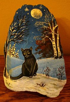 Black Cat painted on a river rock.