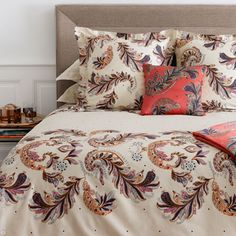 Parure Bed Linens by Yves Delorme is printed with large and small patterns. Large feathers/paisleys decorate duvet covers along the foot of the bed and pillow shams while tiny blue diamonds are sparsely printed on fitted sheets.