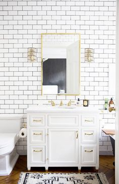 Completely tiled white bathroom with brass accents including mirror and sconce lighting.