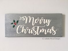 """Festive Silver and White """"Merry Christmas"""" Wood Sign With Holly Leaves- Elegant, Metallic Wood Decor Measures 12"""" by 5"""". This silver and white Christmas sign will sparkle, but not too much! The silver is elegant, but not gaudy and the white paint pops clearly and cleanly on the canvas. Just a splash of color in the holly leaves finishes the piece. My canvasses are hand made from new floor boards. All pieces are sealed with matte polyurethane for durability without shine or glare. **Please..."""