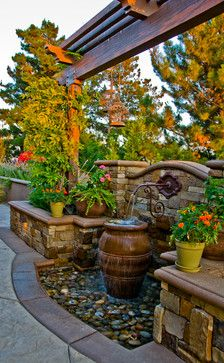 rustic plumbing, ornate fountain pot, stone and woodwork on the pergola all make this look complete