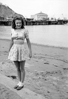 Norma Jeane Baker, future film star Marilyn Monroe, on the beach at Avalon, Santa Catalina Island, circa 1942. Her first husband James Dougherty was stationed on the island's boot camp at the time. In the background is the Avalon Casino.