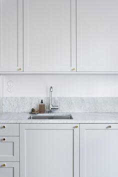 Framed kitchen cabinet doors, golden knob handles, marble worktop