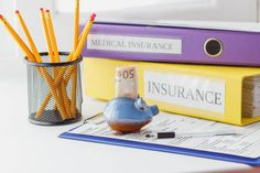 clean insurance form folders pen and piggy bank