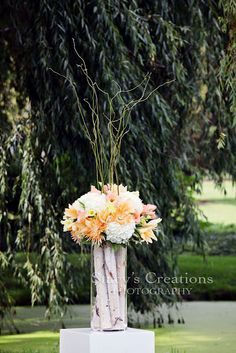 traditional clear vase filled with wood cuts, topped by floral and branches