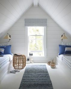 This simple kids bedroom has a beachy feel with its rattan wall sconces, fuzzy blue rug, and rattan side table.