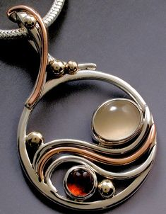 One of a series of jewels called circle wave pendants of silver, copper and gold with moonstone and Orissa garnet made by Jima Abbott.