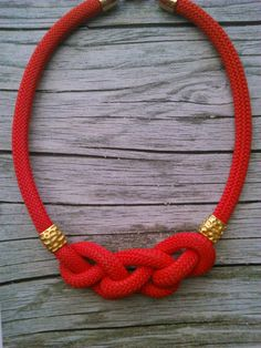 A red climbing braided rope necklace with golden details .