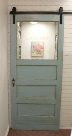 Love it! Old door turned into laundry room barn door. #farmhouse #ad #laundryroom #rusticdecor