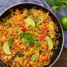 Chicken Pad Thai - this photo shows this classic chicken pad thai recipe in a skillet garnished with lime wedges and cilantro and ready to be served