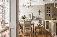 The kitchen-dining room.  Kitchen set, Aster.  Dining table, Labarère, surrounded by chairs and armchairs, Mis en Demeure.  The same measurements - the console wall.  Paired chandeliers, Judeco.  Bra - antiques from France.