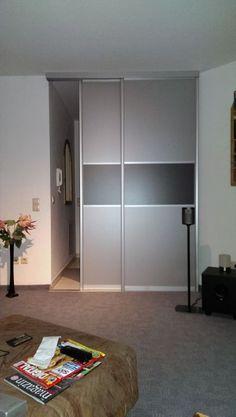 Die Schiebetür als Raumteiler in den Füllungen Graphit Metallic und Aluminium trennt den Eingangs- vom Wohnbereich stolvoll ab.