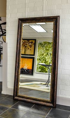 A Large Leaning Floor Mirror In Brown Frame With Touch Of Gold Details