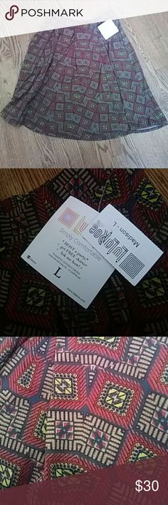 NWT LuLaRoe Madison skirt Dark printed midi skirt with reds, yellow, black and navy throughout. Great winter colors. Stretch waist size large. Feel free to offer LuLaRoe Skirts Midi