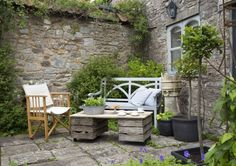 Courtyard garden boasts stone walls, scented plants and potted evergreens. Once a faded lawn​, this small courtyard garden is now a blissful outdoor sitting room.