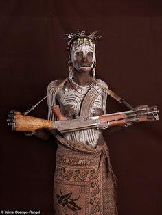 Africa |  Mursi woman holding a AK-47 weapon.  Omo Valley, Ethiopia.