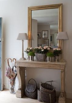 Hallway console with a touch of Belgian styling, gold mirror and baskets