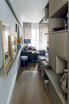 Corredor | Localizado na entrada do apartamento, recebeu estante de marcenaria e banco com futons, para a mesa de jantar (Foto: Edu Castello/Editora Globo)