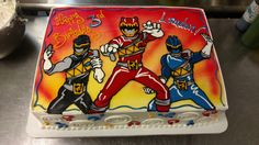 This half sheet Power Rangers cake features airbrush accents and hand illustrated Rangers.