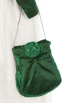 A green satin and whitework ensemble, circa 1820. the spencer bodice in two shades of green satin, with puffed mancherons, trimmed in blonde silk lace, with matching waist belt, reticule with cut steel button closure and chain; pumps labelled 'Rimmevaux, Rue de la Ferme des Mathurins, Paris'; assorted satin bows and a band (possibly for a cap); the muslin skirt with deep bands of whitework and ruffled bands to hem