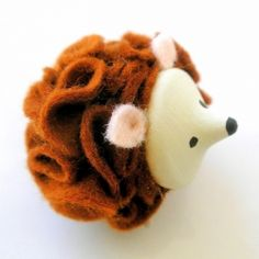 Felt ruffles have been added around a little wooden acorn painted playfully with a cute face.