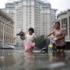 Una bambina con due teiere insieme a donna in una strada alluvionata #Tianjin #Cina