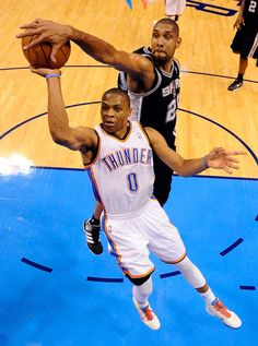 Tim Duncan Photos Photos - Russell Westbrook #0 of the Oklahoma City Thunder goes up for the shot as Tim Duncan #21 of the San Antonio Spurs attempts to block it from behind in the first half in Game Five of the Western Conference Finals of the 2012 NBA Playoffs at Chesapeake Energy Arena on May 31, 2012 in Oklahoma City, Oklahoma. NOTE TO USER: User expressly acknowledges and agrees that, by downloading and or using this photograph, User is consenting to the terms and conditions of the…