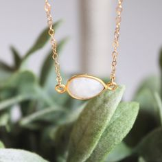 """White """"Rainbow"""" Moonstone Necklace A delicate moonstone, teardrop shaped pendant wrapped onto a dainty 14k gold filled chain.   -Gold-filled components are legally required to contain 5% or 1/20 gold by weight. This 5% is then described by the karatage of the gold alloy. This necklace is made out of 14 karat gold filling and meets the 5% standard. LucyMint Jewelry Necklaces"""