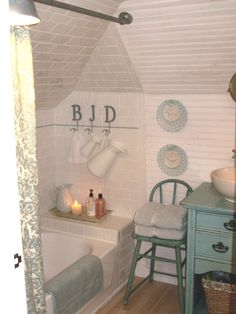 Tiny cottage attic bathroom-- love the chair, table vanity and plates, very cozy feeling & great use of a small space.