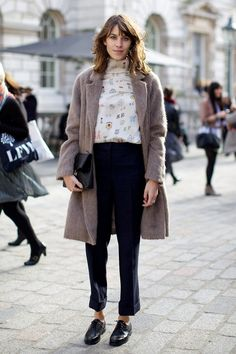 Alexa Chung wears a printed silk turtleneck, fuzzy coat, cropped trousers, oxfords, and a clutch