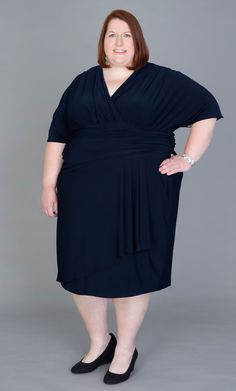 """Aptly named, Real Curve Cutie Danica (5x,  5'5"""") is looking smart in the Danika Draped Dress.  This classic navy blue dress has a hint of gold shimmer running throughout.  Smooth, curve skimming fabric and an asymmetrical front detail makes this dress a winner.  #KiyonnaPlusYou #Kiyonna #PlusSize"""