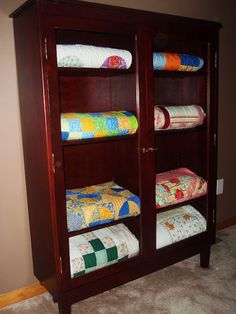 quilts neatly folded and stacked in a cupboard. isn't it a