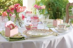 Delicate china, an array of crystal, and flowers in varying shades of pink combine for an inviting tea table.