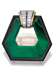 18 KARAT GOLD, MALACHITE, ONYX AND DIAMOND BROOCH, CARTIER, FRANCE The hexagon-shaped malachite frame bordered by onyx, the top set with baguette diamonds weighing approximately 1.20 carats, signed Cartier, numbered 26590 and 203, with French assay and indistinct workshop marks.