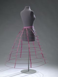 1860-65 unusual purple cage crinoline. of cotton, wool, silk, steel and brass. Purple silk waistband with cream cotton lining, closed at the front with a brass metal hook and three eyes. 8 purple wool tapes suspending 12 steel hoops wrapped in purple wool. The hoops are attached to the straps with brass clamps. The hoops are closed in the front with two brass clamps that allow them to be adjusted in size. The two upper hoops are open at the front for entry. Amsterdam Museum.
