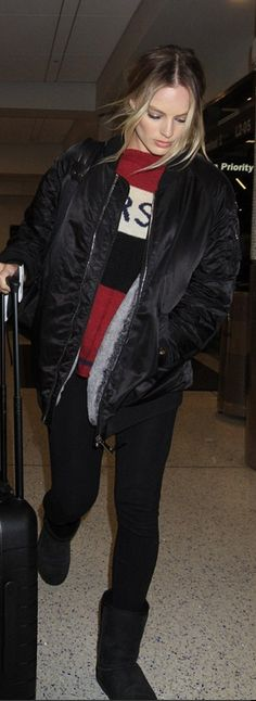 Who made Margot Robbie's black ankle boots, red stripe sweater, bomber jacket, and luggage?