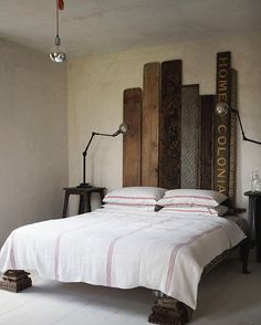 #Baileys steel frame #bed, with a #headboard made from an old shop sign, carved #Indian panels and ware boards. The bedding is a #Hungarian cart cover. #baileyshome